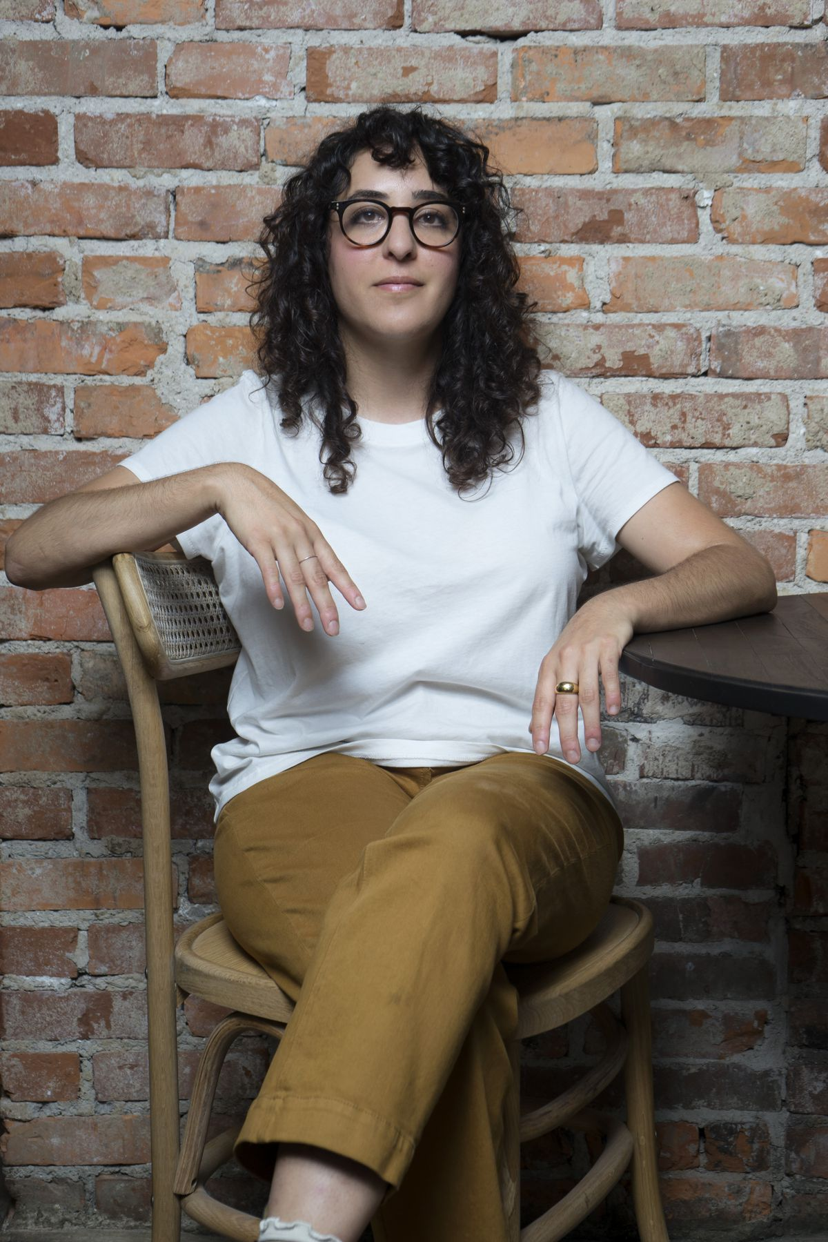 Pastry chef Sarah Piligian sits on a chair with a brick wall background.