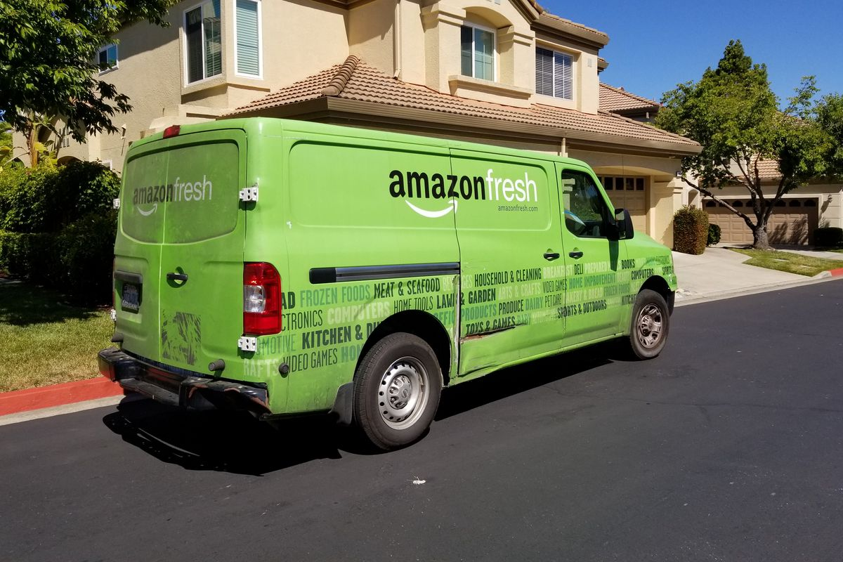 An Amazon Fresh delivery van stopped outside a suburban home.