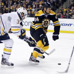 Boston Bruins' Joe Corvo (14) loses his stick while defending against Buffalo Sabres' Jordan Leopold (3) in the first period of an NHL hockey game in Boston, April 7, 2012.