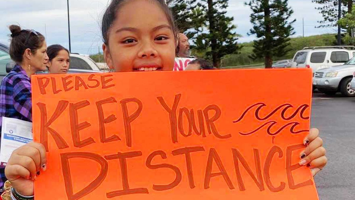"""A young girl holds a sign that reads, """"Please keep your distance ocean length."""""""