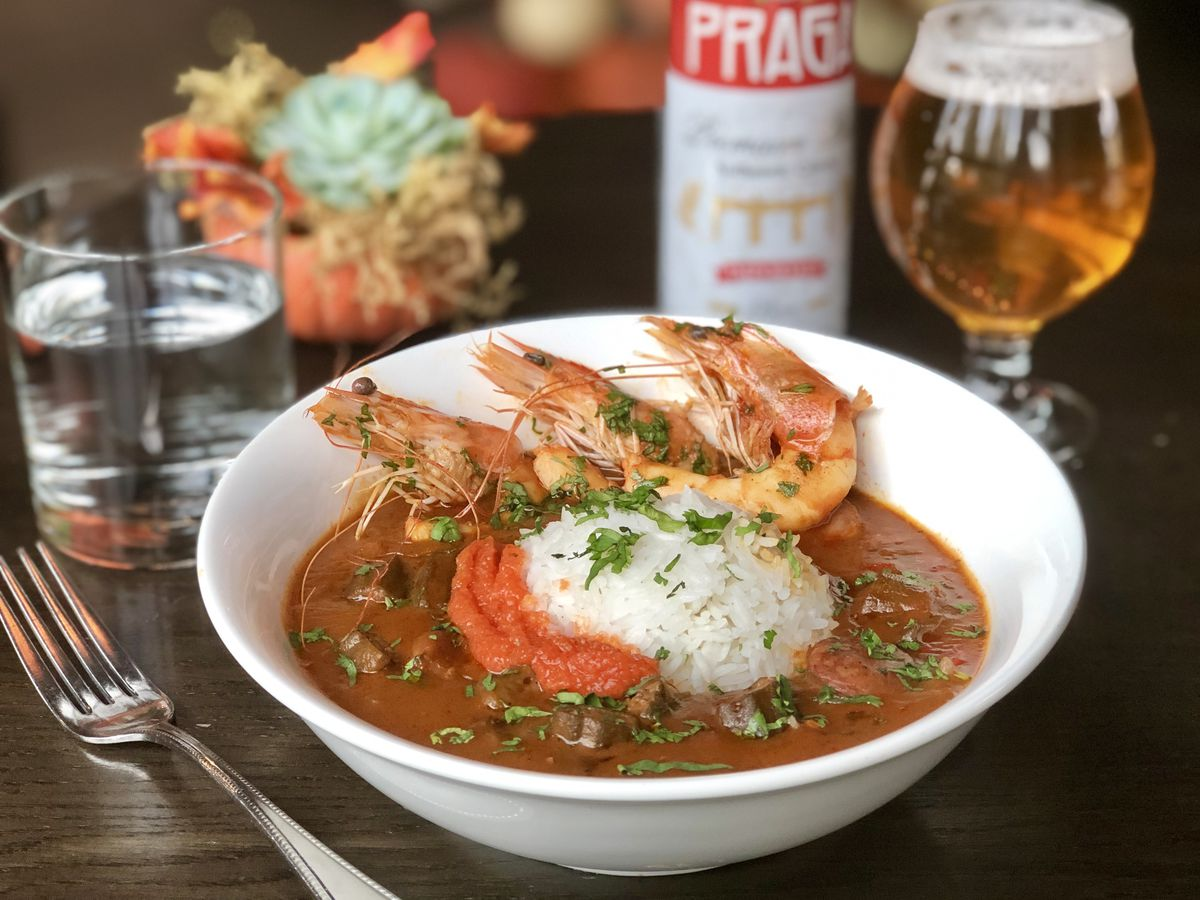 A bowl of shrimp gumbo with rice and a glass of beer in the background.