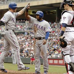 Texas Rangers' Josh Hamilton, left, celebrates with teammate Elvis Beltre in front of Minnesota Twins catcher Joe Mauer after scoring on Hamilton's two-run home run against Twins pitcher Glen Perkins during the eighth inning of a baseball game on Sunday, April 15, 2012, in Minneapolis. The players were all wearing No. 42 in honor of Jackie Robinson Day. The Rangers defeated the Twins 4-3.