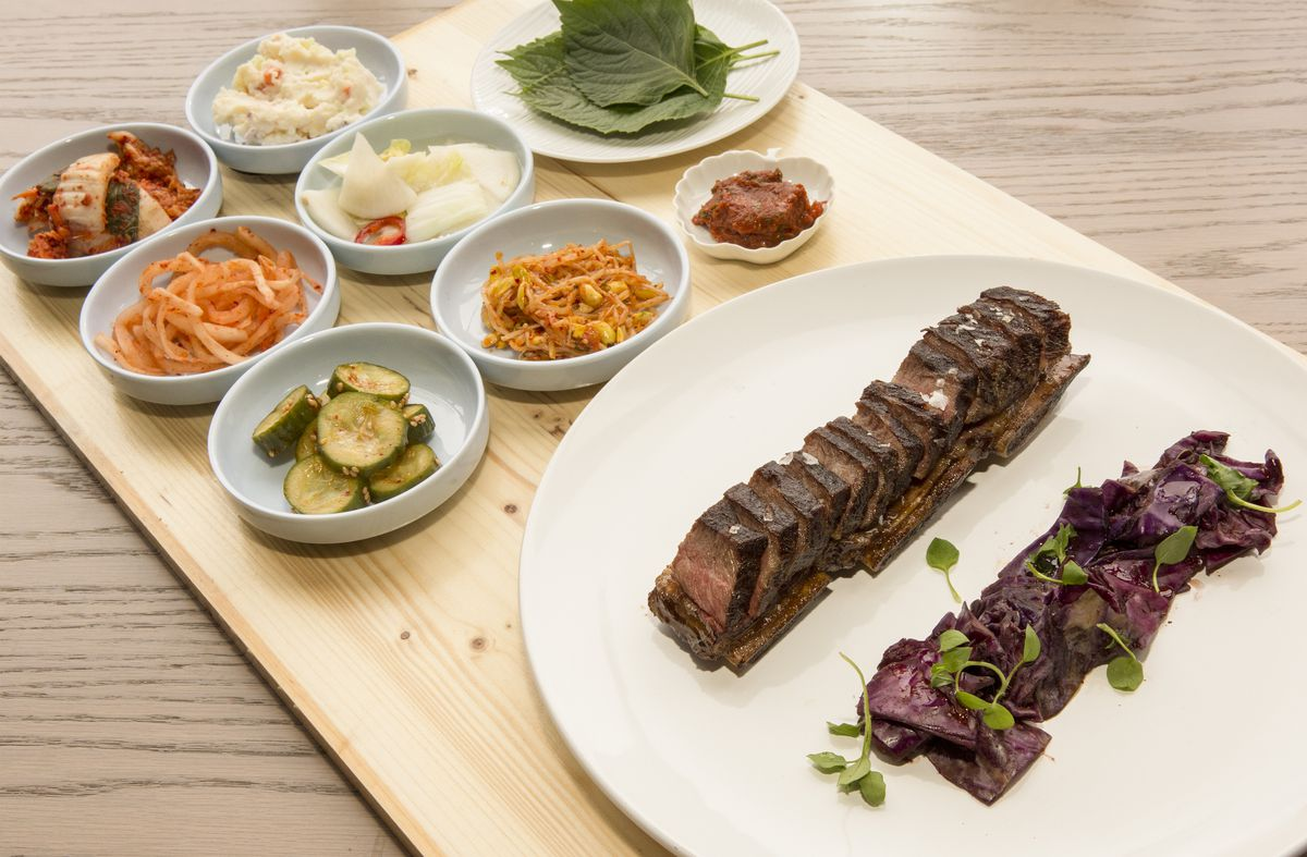 A wooden board holds a round white plate that contains sliced kalbi and eight smaller dishes that hold various colorful banchan.