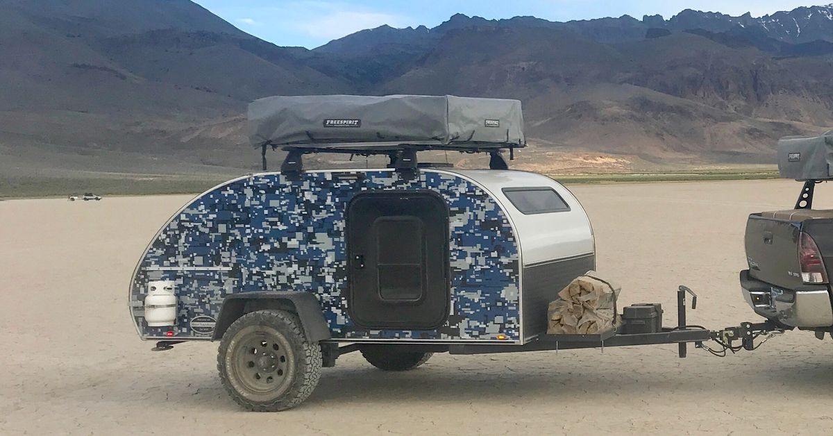 Custom teardrop trailer uses a rooftop tent to camp a family