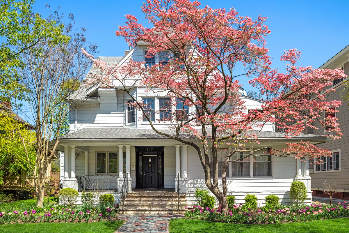 A two-story Colonial Revival home with a white paneled facade and Doric columns in its porch.