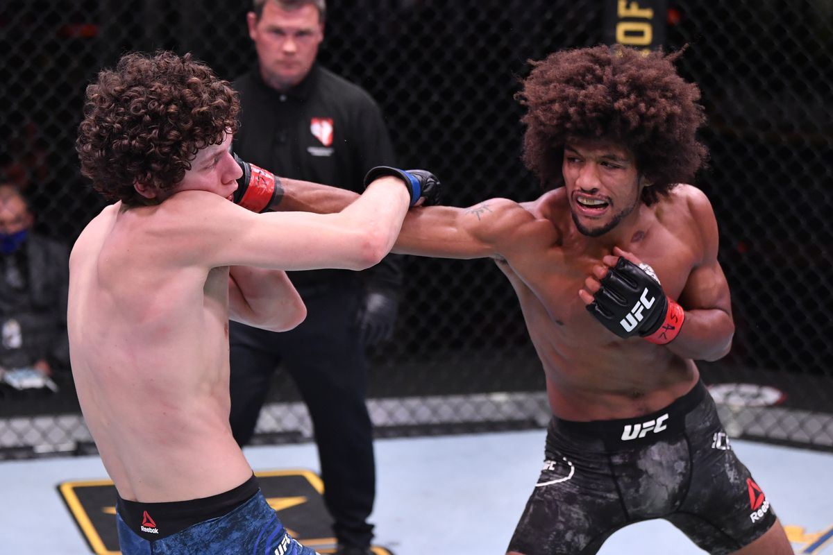 Alex Caceres punches Chase Hooper in their featherweight bout during the UFC 250 event at UFC APEX on June 06, 2020 in Las Vegas, Nevada.