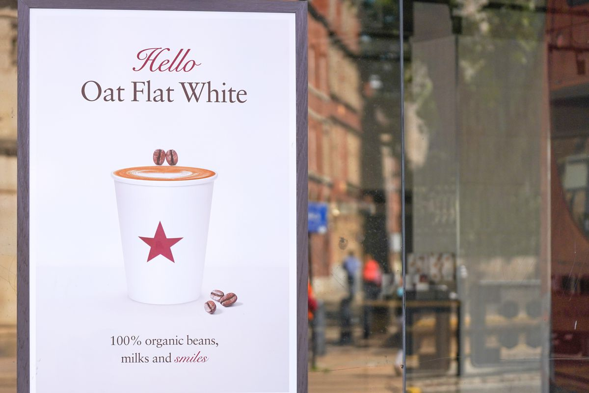 """A Pret a Manger cafe window with a poster hanging that reads """"Hello Oat Flat White"""""""