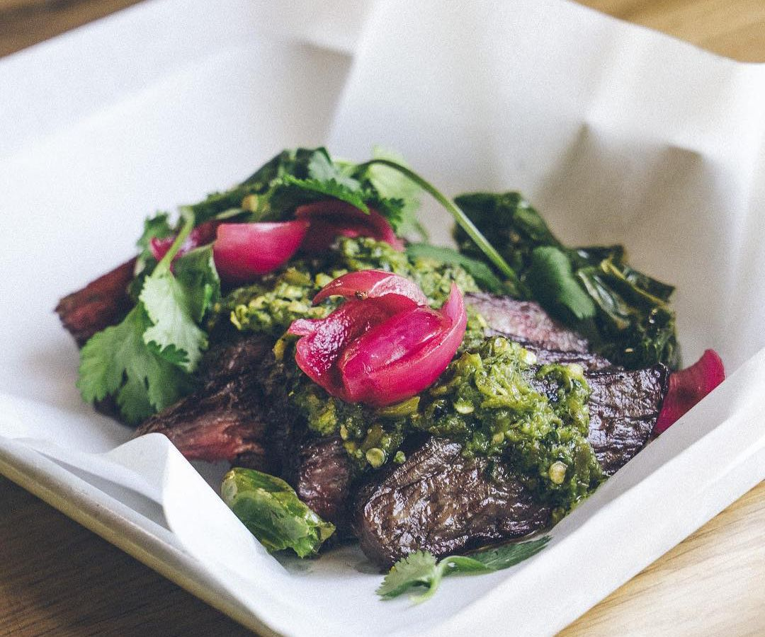 Slices of bavette steak topped with chunky green salsa, purple pickled pearl onions, and cilantro on a sheet of white paper on a tray