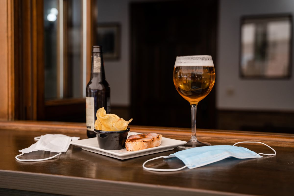 Two light blue cloth masks sit on a bar, next to a plate of chips, toasted bread, a full glass of beer, and a bottle of beer