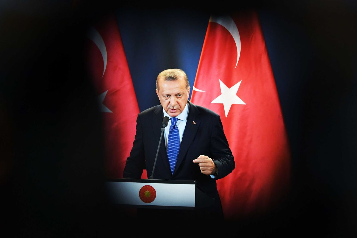 Turkish President Recep Tayyip Erdoğan speaks standing in front of Turkish flags.