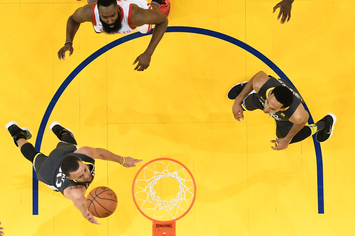 A basketball player goes up for a basket