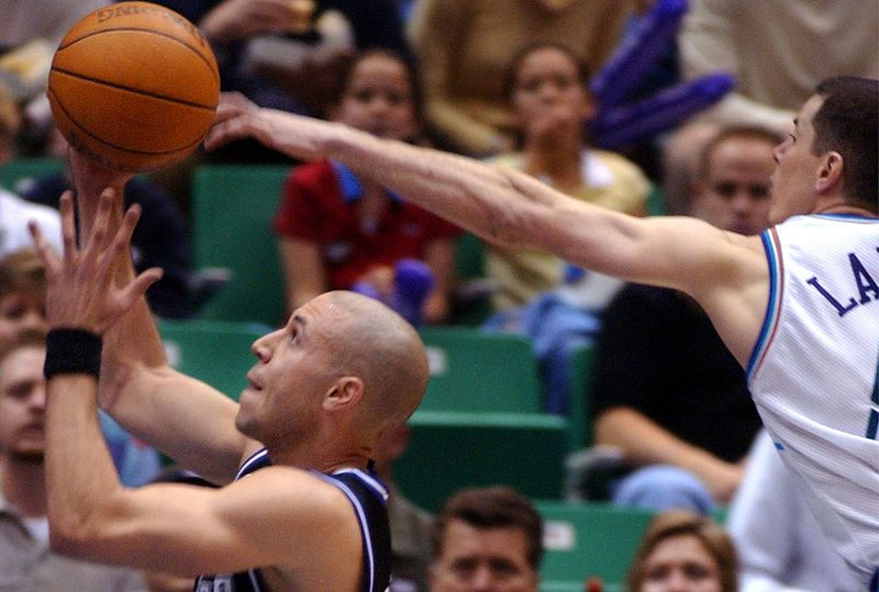 Utah Jazz' Rusty LaRue reaches over Sacramento Mike Bibby's back to block the ball during thethird playoff game between Utah Jazz and Sacramento Kings. The Kings beat the Jazz 90-87. Delta Center, Saturday, April 27, 2002. Photo/Johanna Workman (Submission date: 04/27/2002)