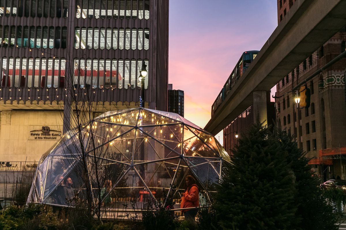 People stand inside a plastic geodesic dome installed along the Woodward Esplanade for Detroit's holiday market at sunset.