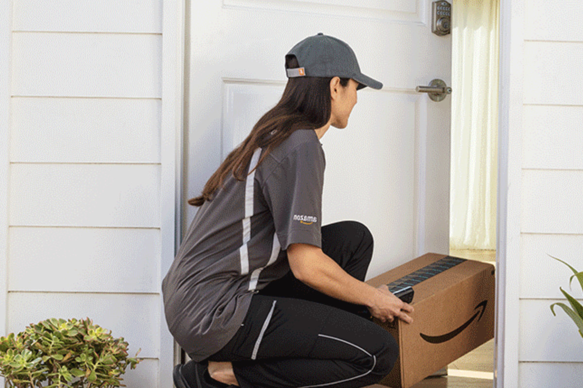 An Amazon delivery person opening a house's front door and putting a box inside