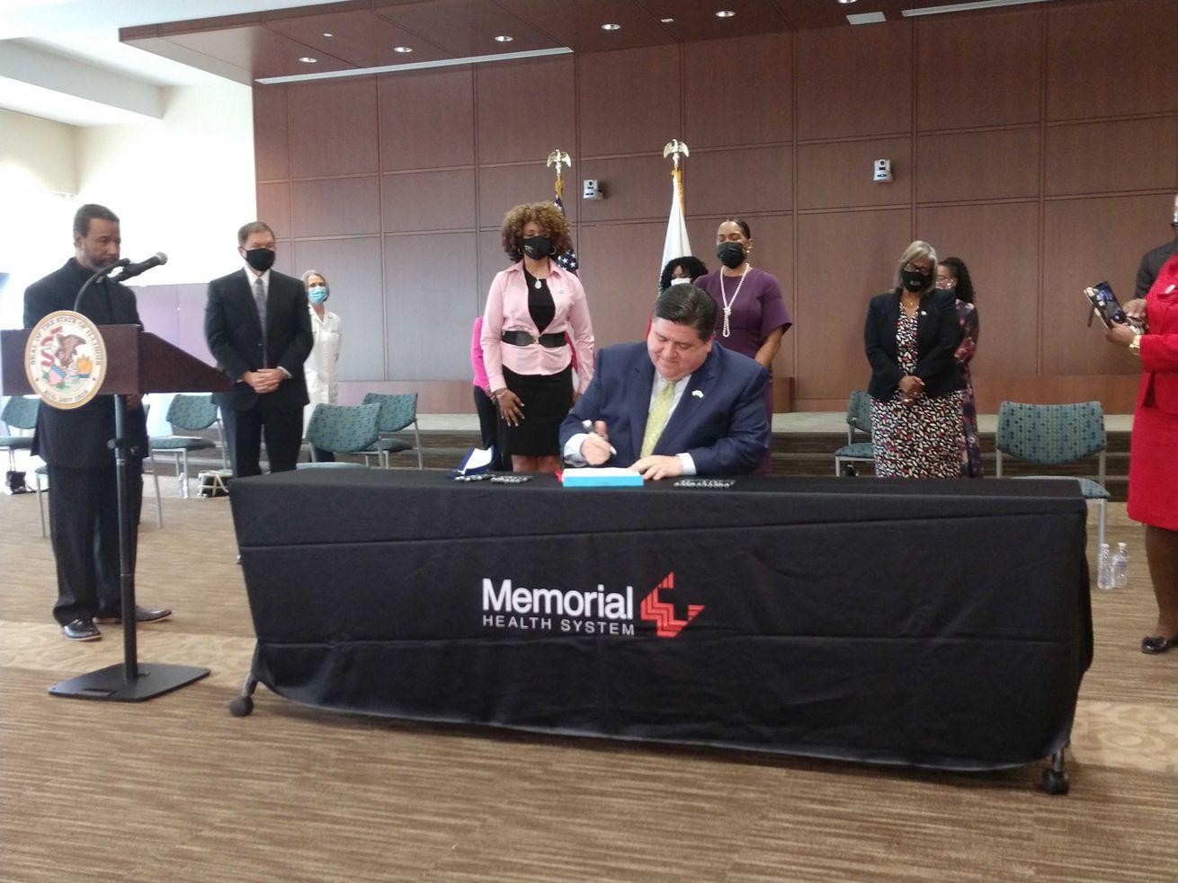 Gov. J.B. Pritzker signs the health care reform bill into law Tuesday.