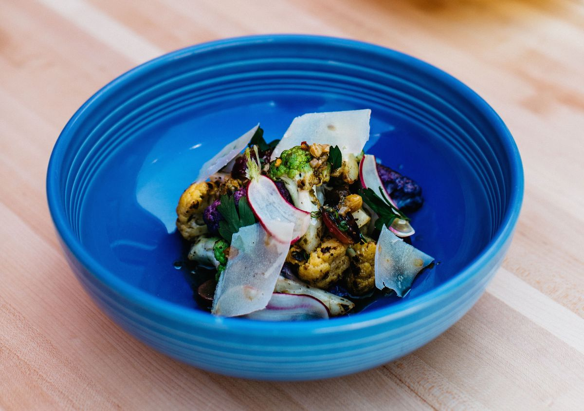 A blue bowl with a cauliflower dish topped with shaved cheese.