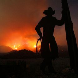 An iron cowboy is backlit by the Mill Flat fire as it continues to burn above New Harmony Sunday night. Firefighters and aircraft were to resume battling the blaze Monday morning.