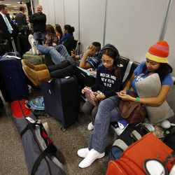Nelly Perea and her daughter Camila wait at Salt Lake City International Airport during a storm, Thursday, Dec. 19, 2013. They are hoping to make it home to Columbia.
