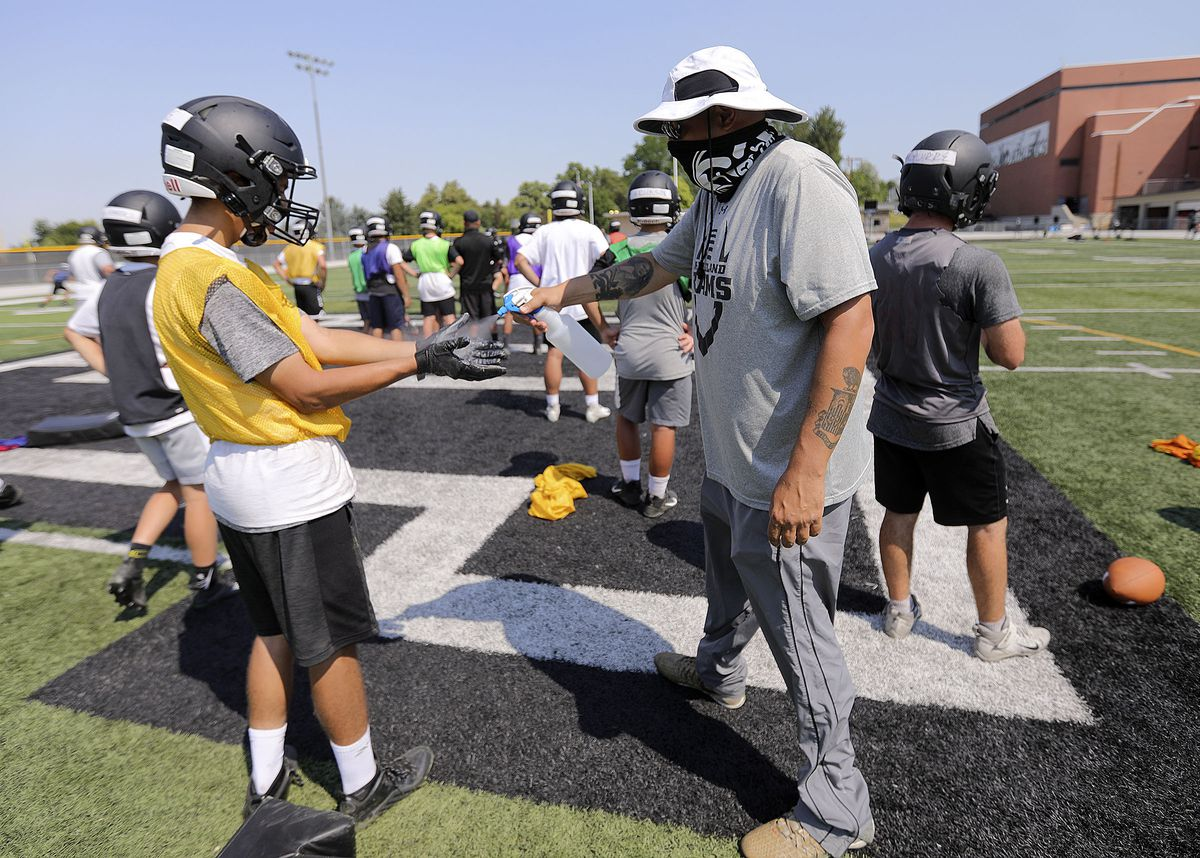 Angel Price, left, gets some hand sanitizer from assistant coach Jon Price during football practice at Highland High School in Salt Lake City on Tuesday, July 21, 2020.