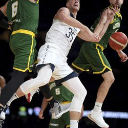 United States' Mason Plumlee, center, battles for the ball against Australia's Andrew Bogut, left, during their exhibition basketball game in Melbourne, Thursday, Aug. 22, 2019.