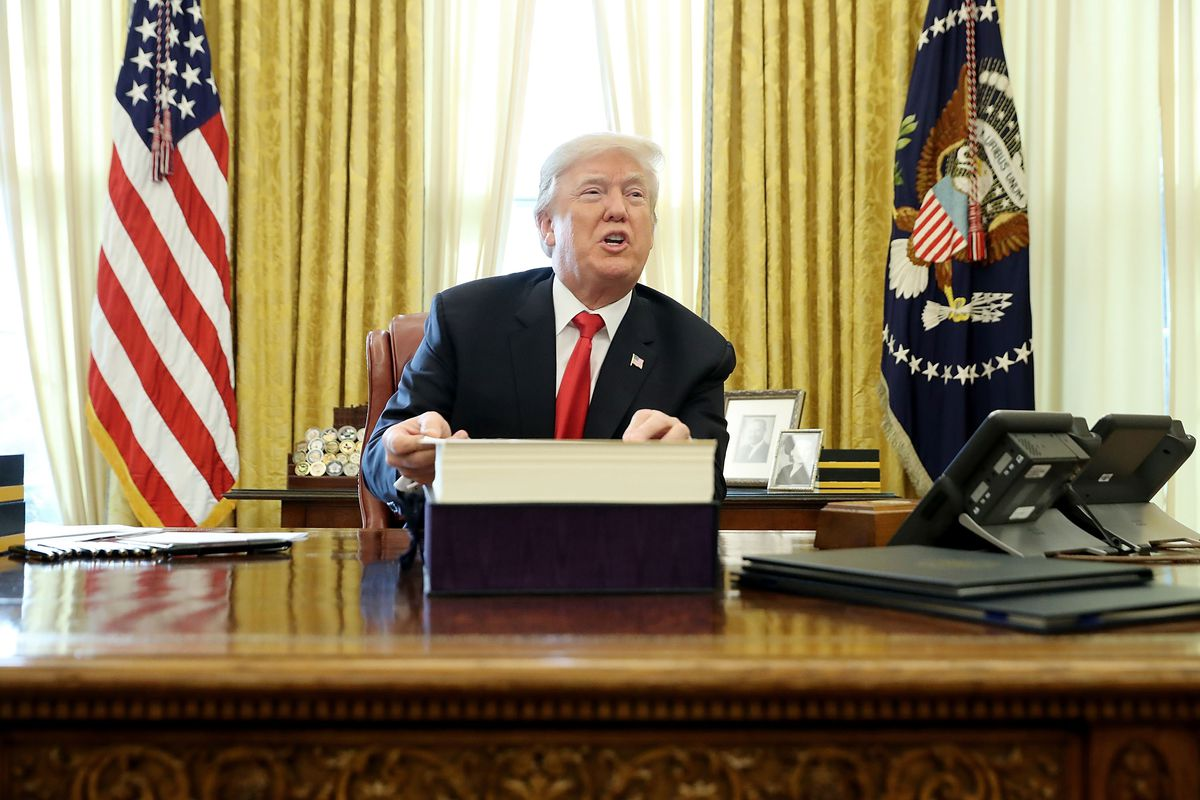 President Donald Trump speaks with reporters after signing the Tax Cuts and Jobs Act into law in the Oval Office in December 2017.