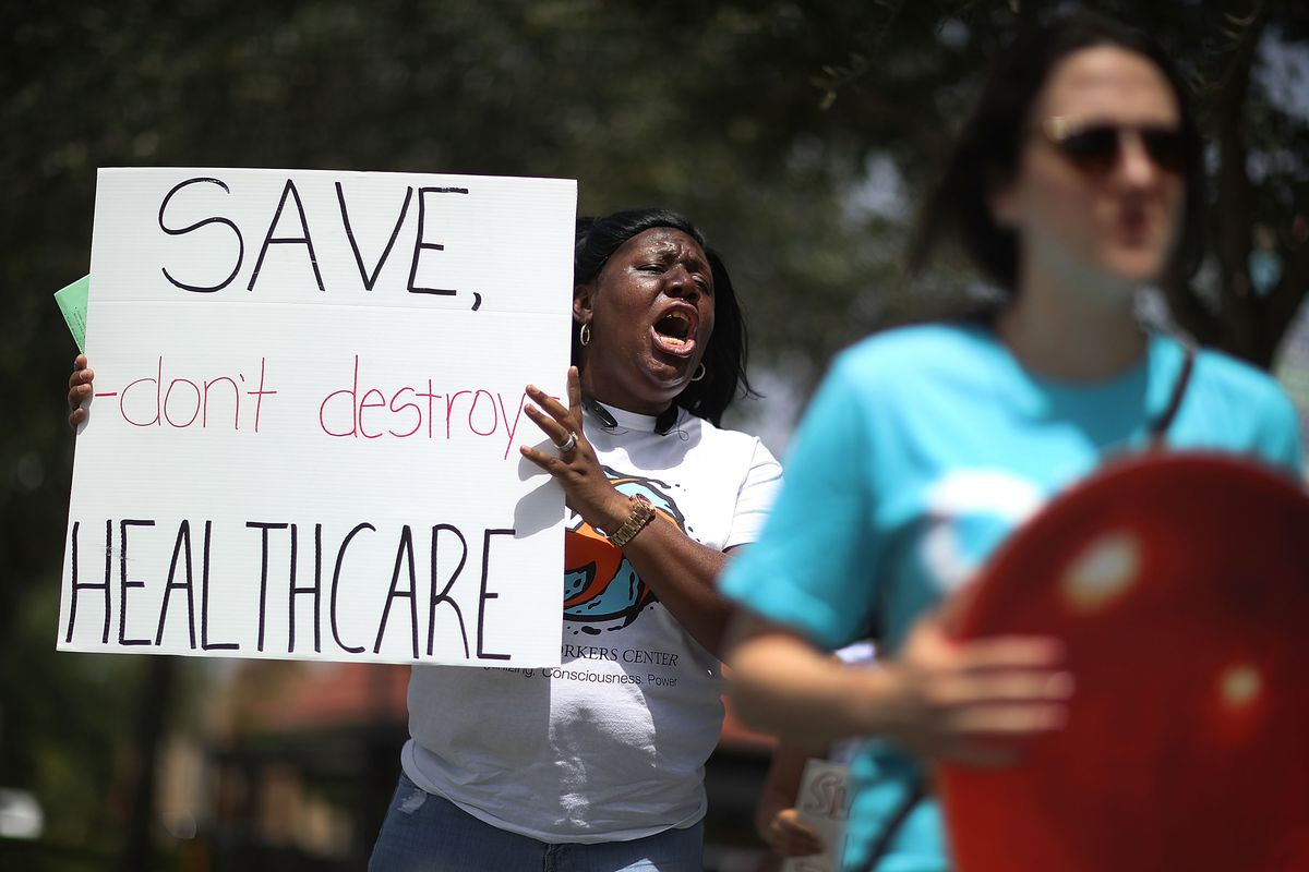 Protesters oppose Rep. Carlos Curbelo's vote to repeal the Affordable Care Act in Miami in August 2017