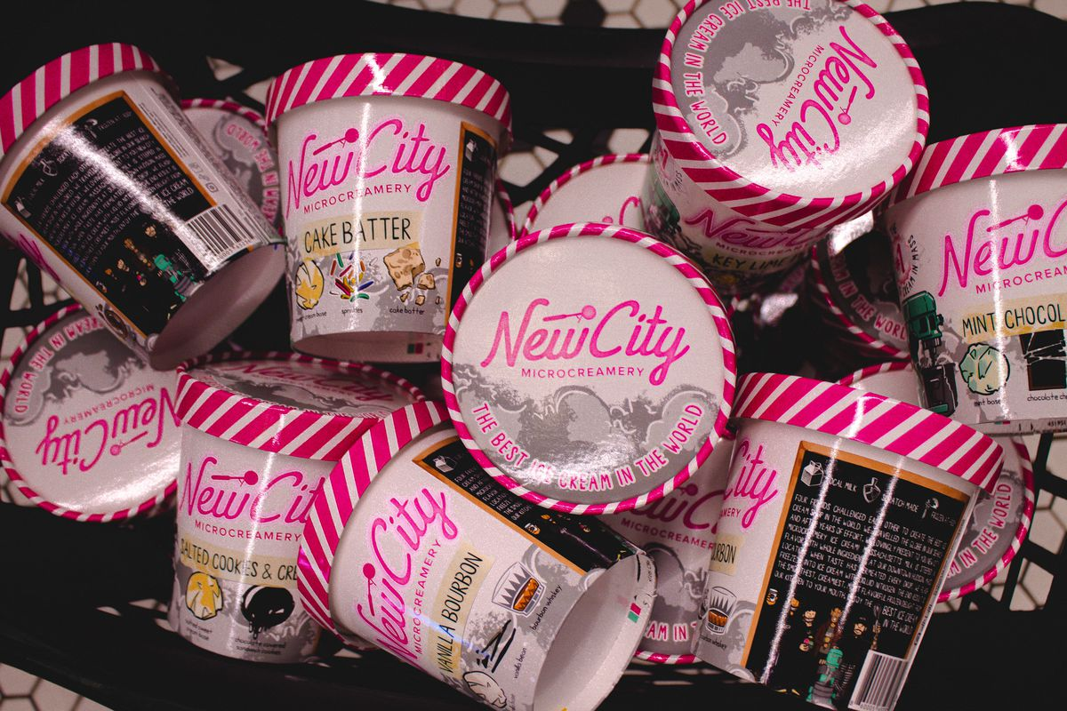 Overhead view of a jumble of ice cream pints with black, white, and bright pink art and a cursive pink logo reading New City Microcreamery