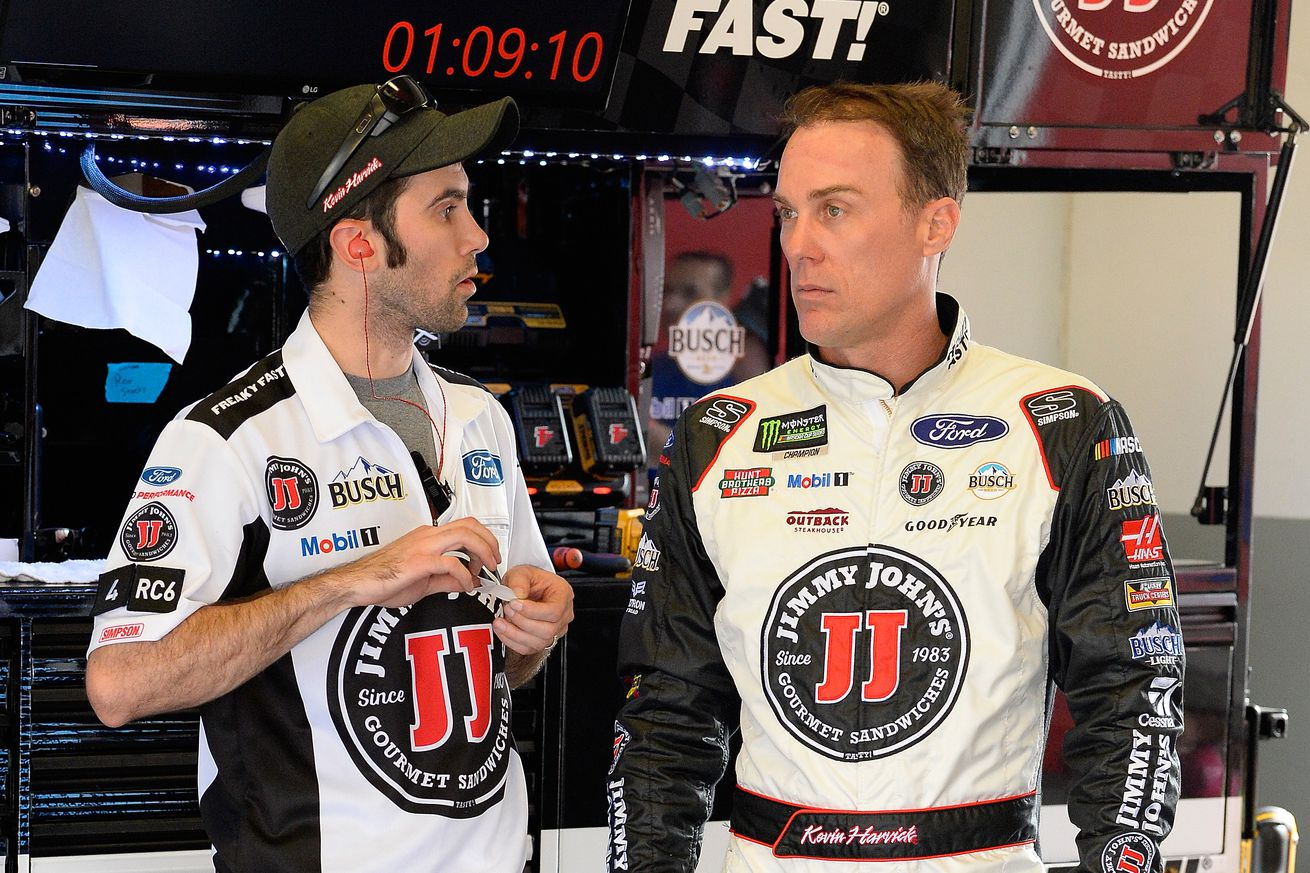 Kevin Harvick (right) talks with a Stewart-Haas Racing crew member during practice for the Daytona 500 on Feb. 16, 2018.
