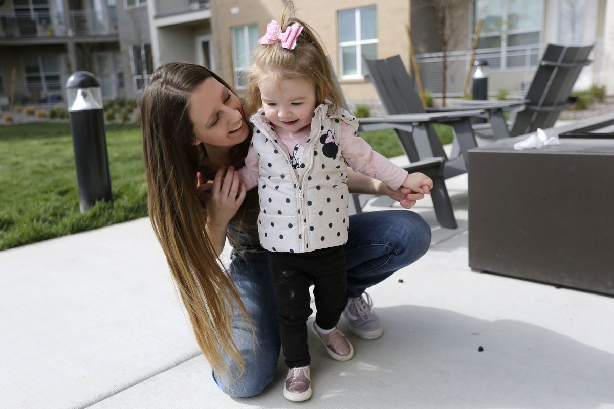 Whitney Beaslin plays with daughter Charlotte outside of their apartment in Sandy on Wednesday, April 1, 2020. Beaslin, a server and a single mom, is worried about getting evicted due to losing work from the COVID-19 pandemic.