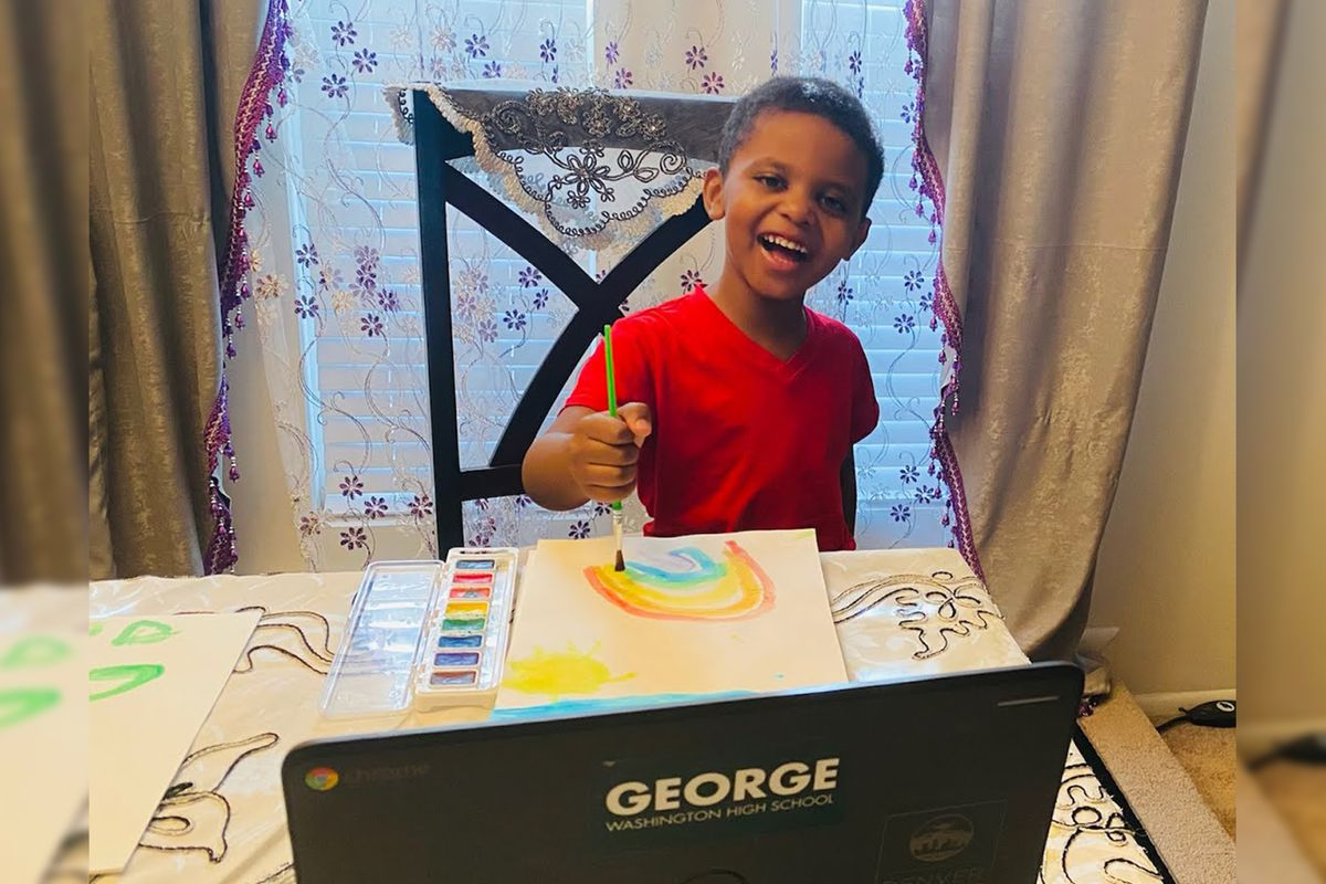 Moumin Elgizoli in front of a laptop painting a rainbow picture.