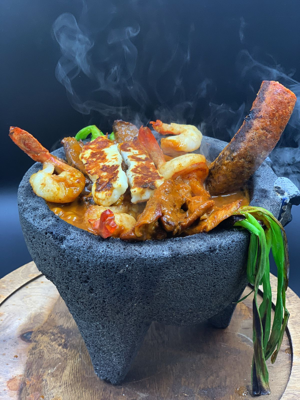 Shrimp, sausage, a browned cheese, and more ingredients sit in a stone molcajete on a wooden tray, with steam coming out from the top of the food