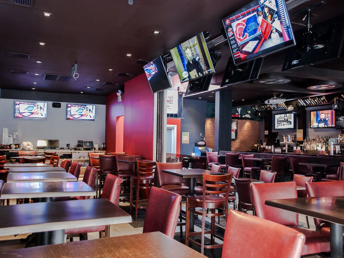 An empty bar with TVs playing sports