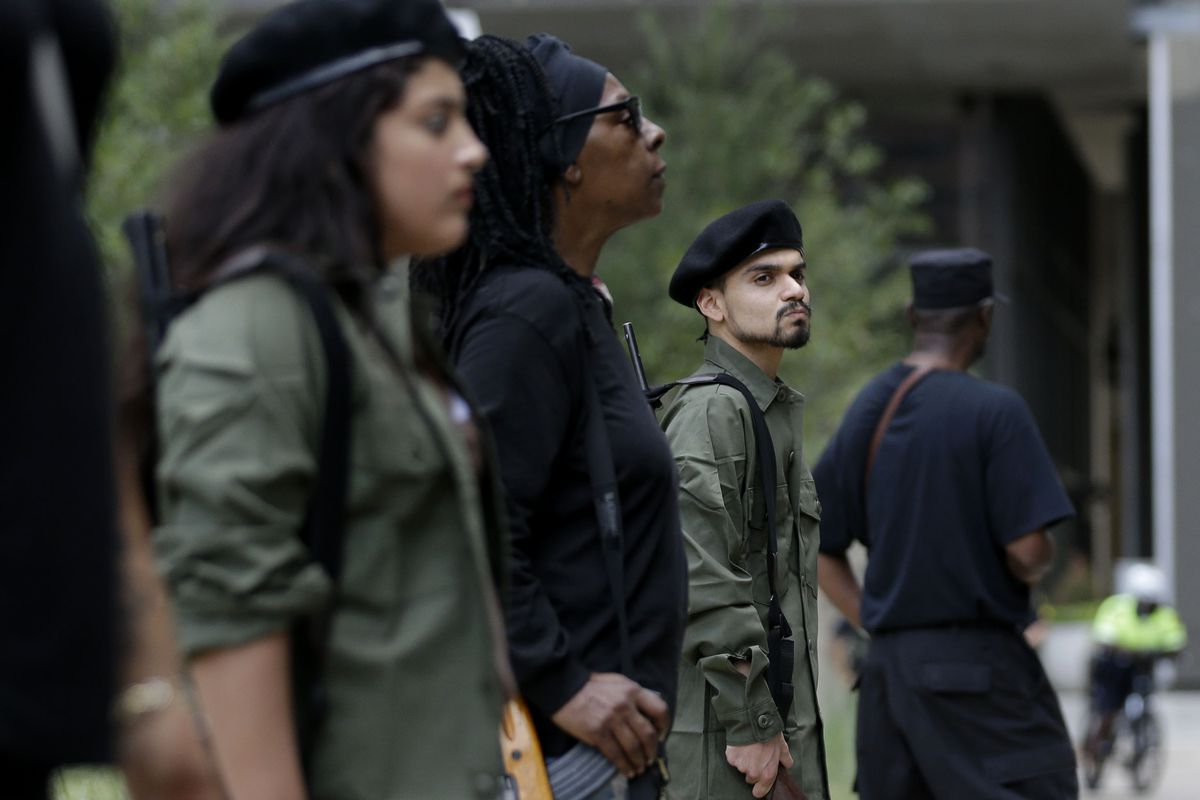 """Member of the Huey P. Newton Gun Club and the Indigenous People's Liberation Party stand outside the federal building during a armed self-defense patrol in Dallas in October 2014. The FBI has — unfairly, some think — identified """"black identity extremists"""