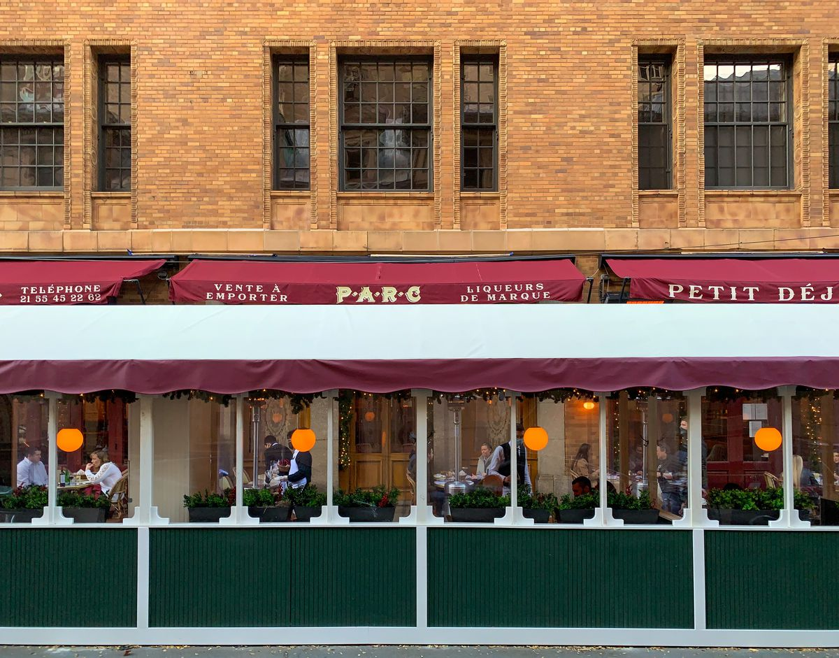 an outdoor dining setup at Parc restaurant with an awning and a green shelter and roof with lights hanging