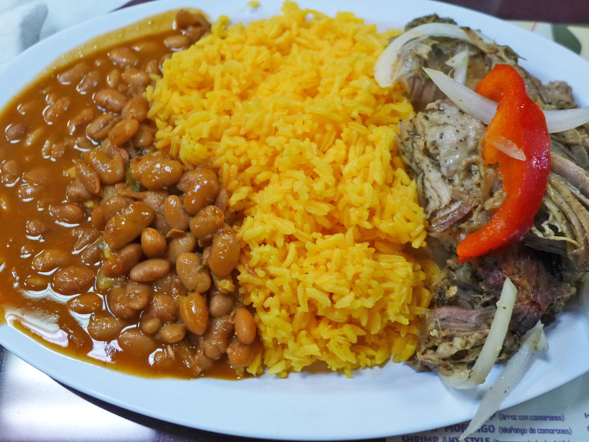 A plate with vertical bands of red beans, yellow rice, and coarse textured pork roast with a slice of red bell pepper on top.