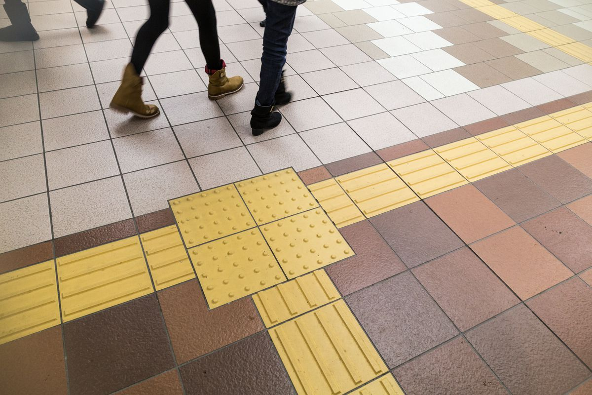 A busy indoor area with bright yellow Tenji blocks that help the visually impaired navigate cities safely.