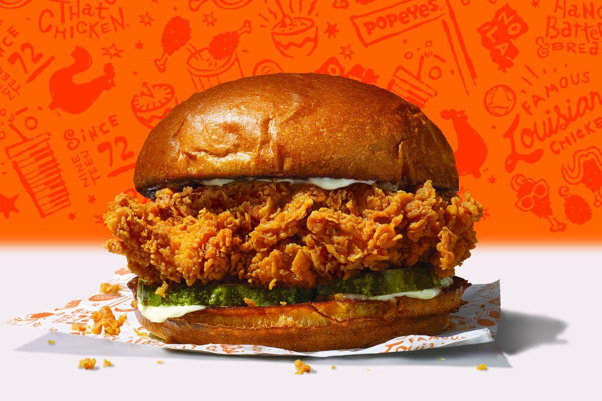Fried chicken sandwich on a bun, sitting atop a wrapper.