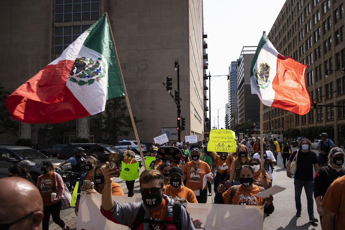 """Activists with immigrant rights organizations and their supporters march from the U.S. Immigration and Customs Enforcement Chicago Field Office to Federal Plaza in the Loop, marking the date on which ICE would have begun its now-postponed """"Citizens Academy,"""" Tuesday afternoon, Sept. 15, 2020.   Ashlee Rezin Garcia/Sun-Times"""