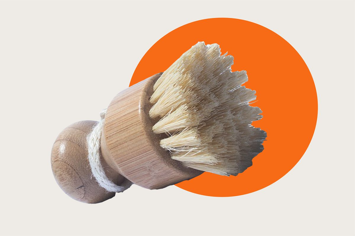 A vegetable brush with a short handle and natural bristles