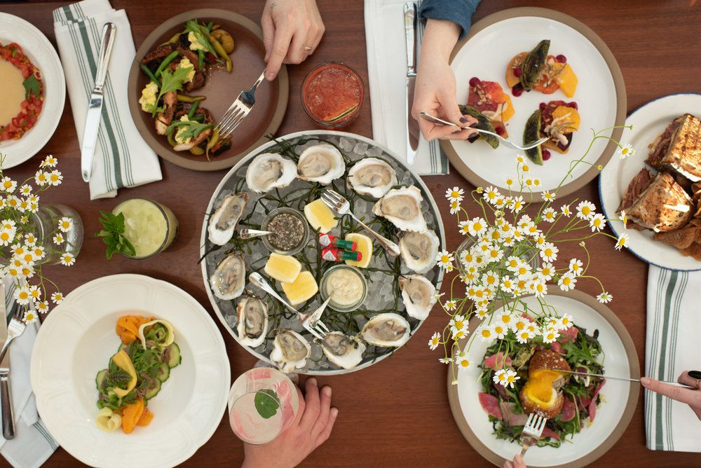 A table spread of oysters and various dishes.