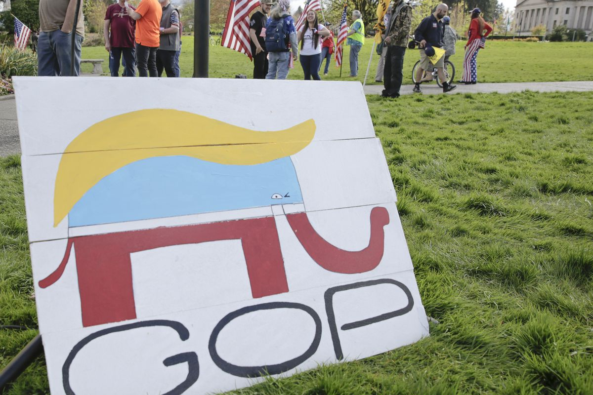 """A sign featuring """"GOP"""" and a Republican Party elephant wearing Donald Trump's hair."""