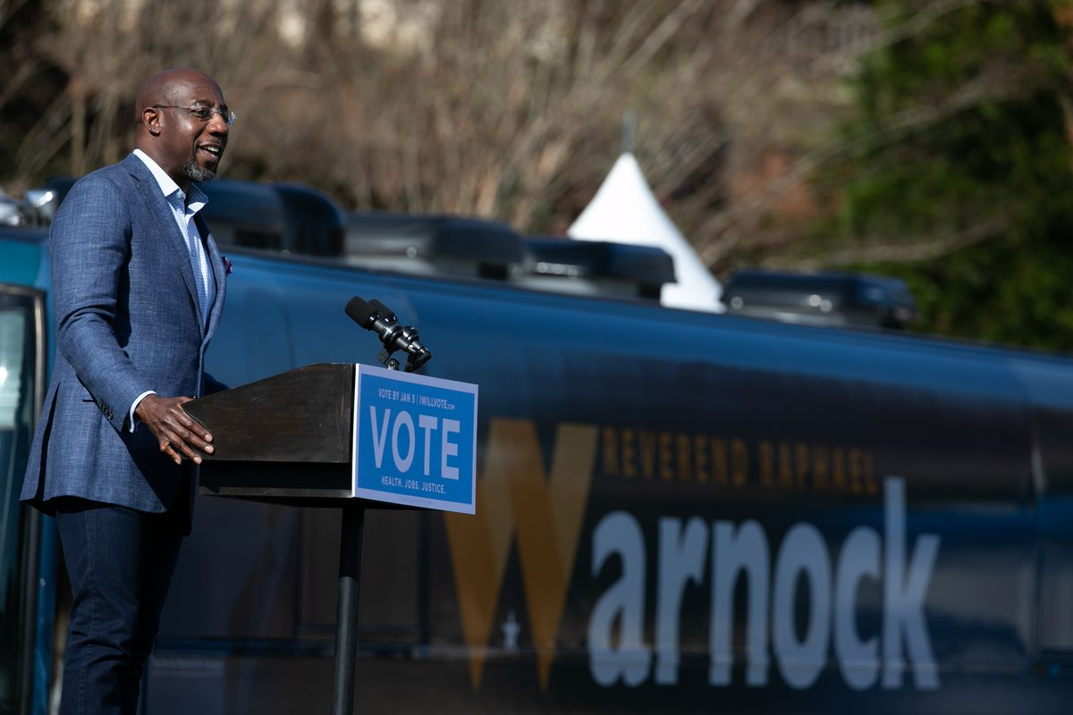 Georgia Democratic Senate candidate Rev. Raphael Warnock addresses the crowd during a drive-in rally at Bibb Mill Event Center on December 21, 2020 in Columbus, Georgia.