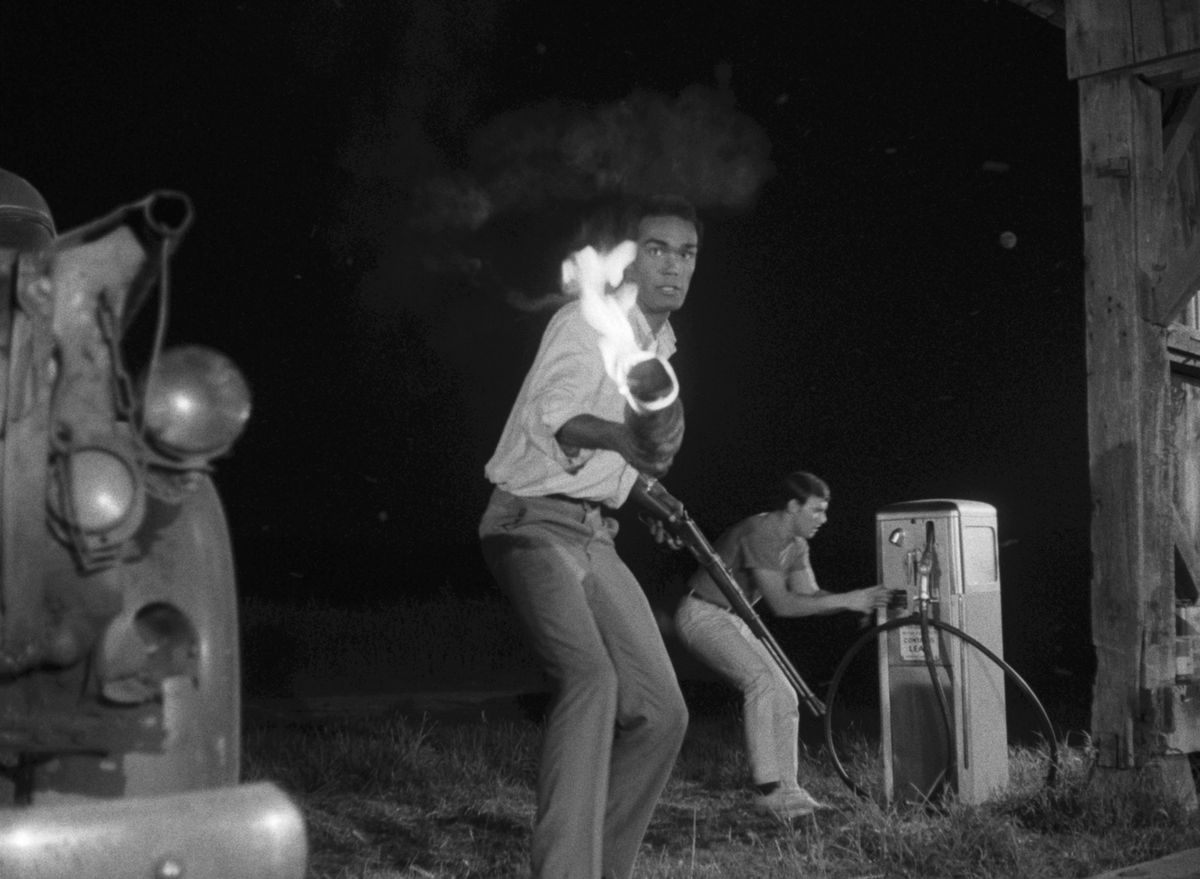 Duane Jones as Ben brandishes a torch at some ghouls