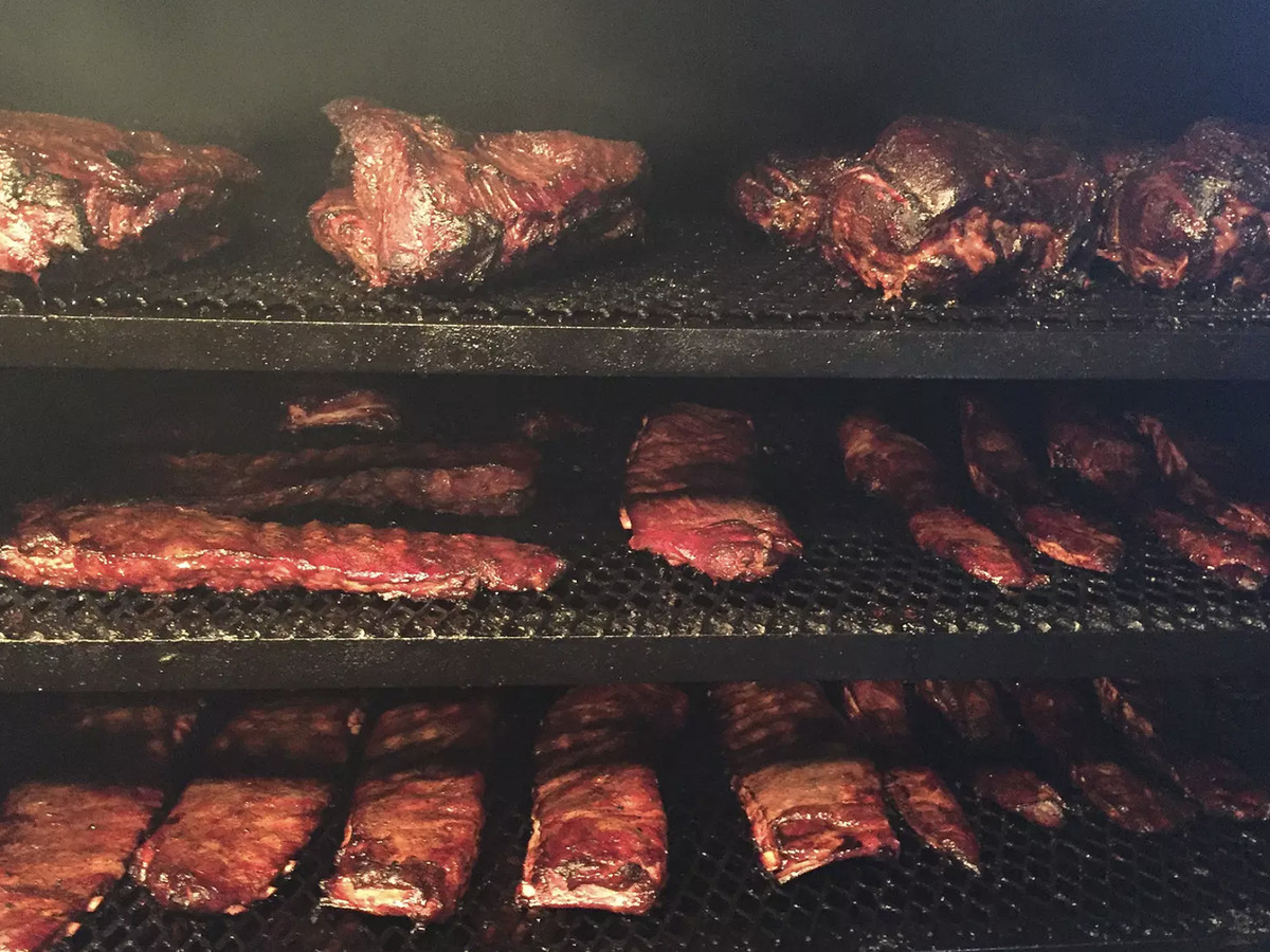 A smoker filled with brisket, ribs, and other slabs of meat, slowly cooking.