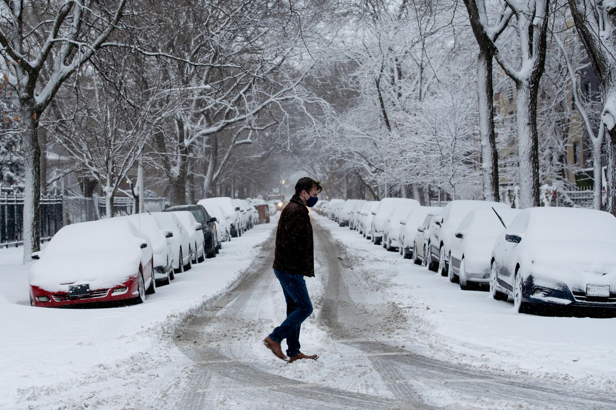 A person crosses the street in Edgewater after more than three inches of snow fell across the Chicago area overnight. More snowfall is possible Tuesday, the weather service said.