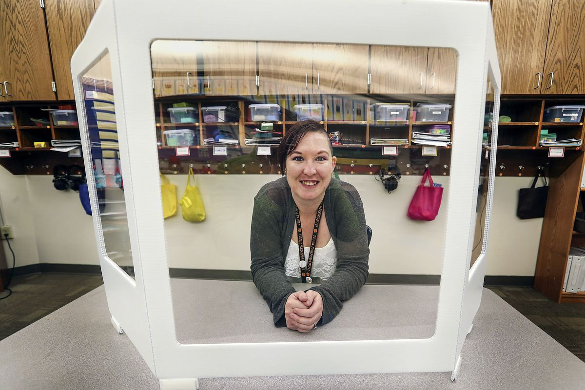 RayShell Shelden, a paraeducator who works with special education students at Philo T. Farnsworth Elementary School in West Valley City, poses for a photo on Tuesday, Feb. 23, 2021, while sitting behind the screen she uses when teaching at the school.