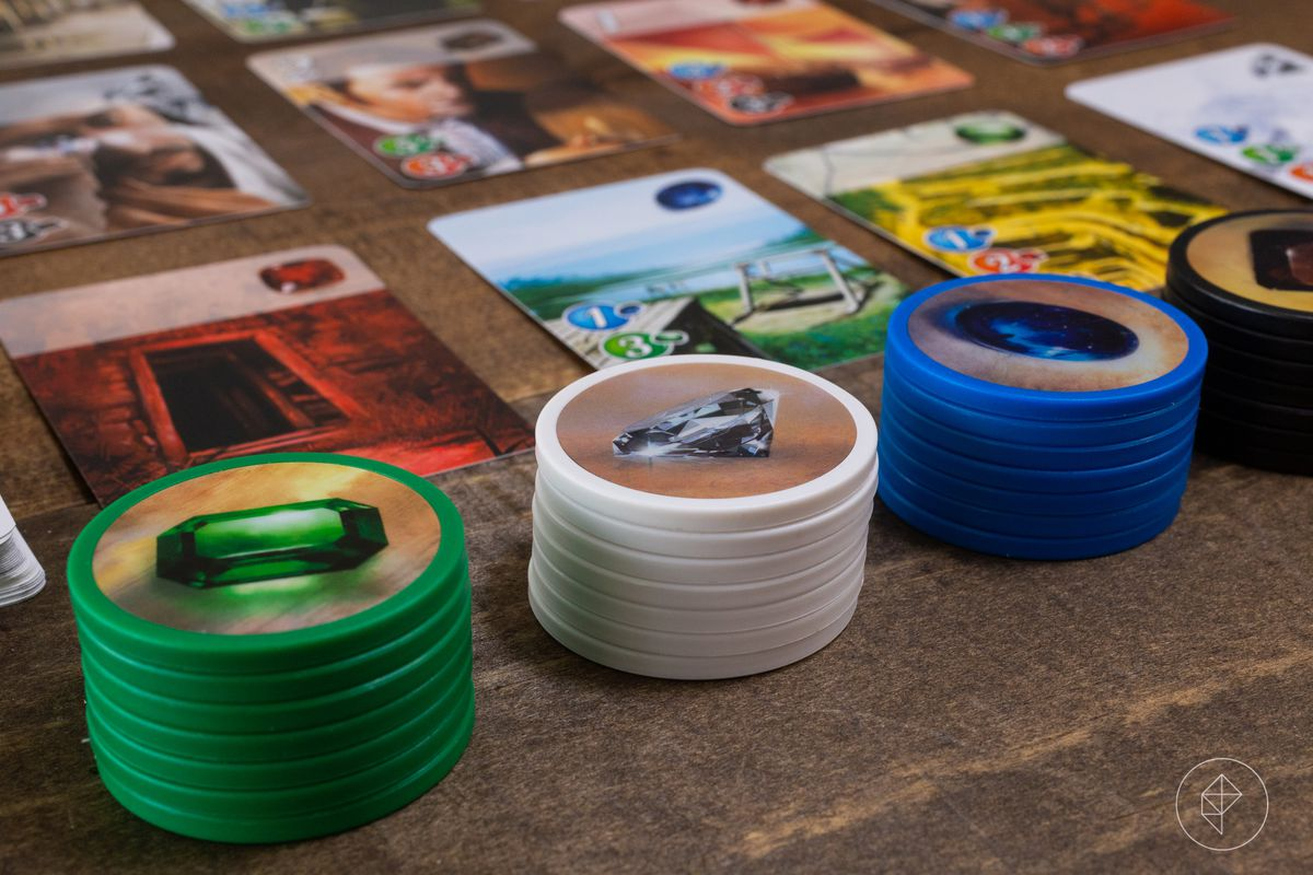 Stacks of gems along the side of the card grid in Splendor.