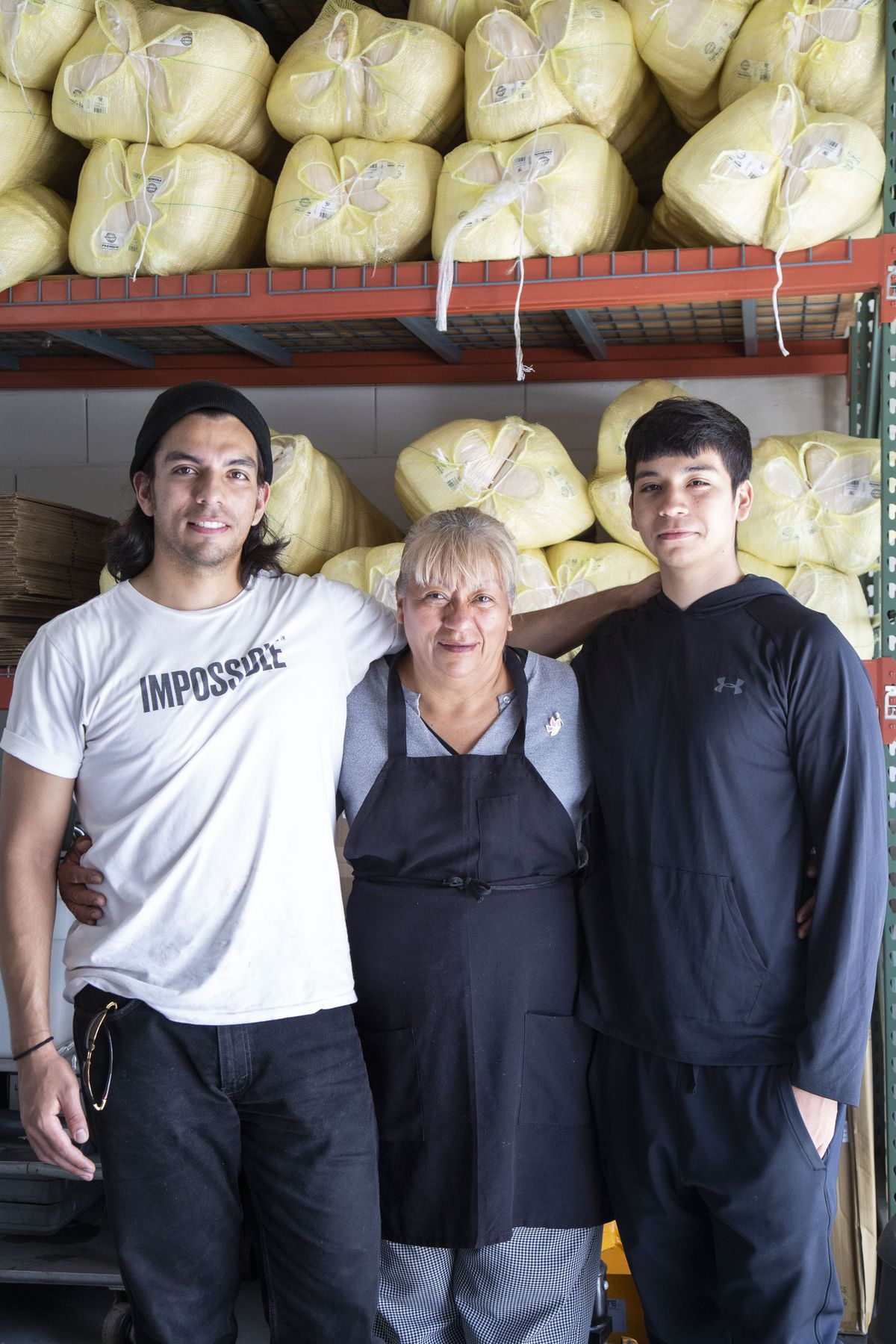 Alicia Villanueva (center) poses at her tamale factory with her sons Pedro Jr. (left), 27, and Pablo (right), 18