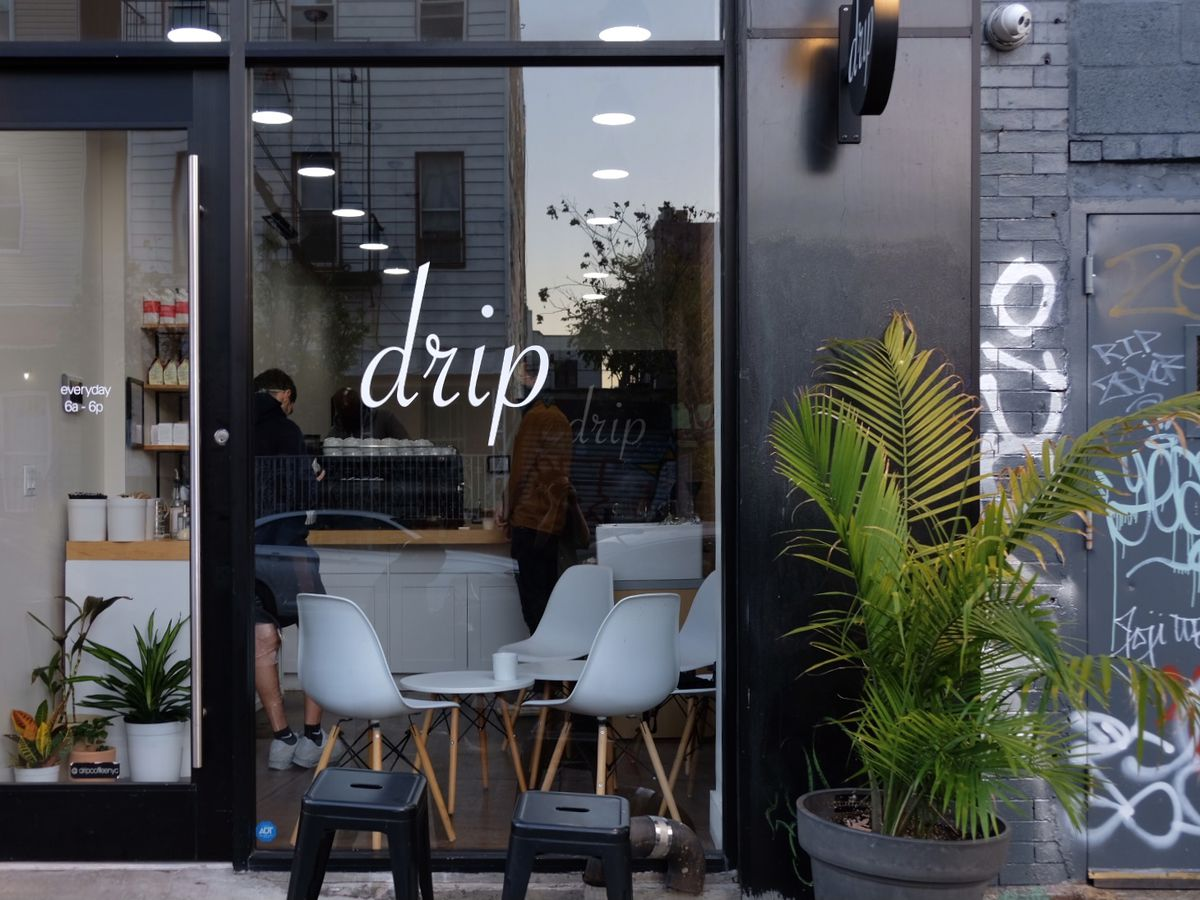 """An exterior shot of the coffee shop with the lowercase name """"drip"""" in white cursive letters on the front window. A white counter and chairs can be seen through the window."""