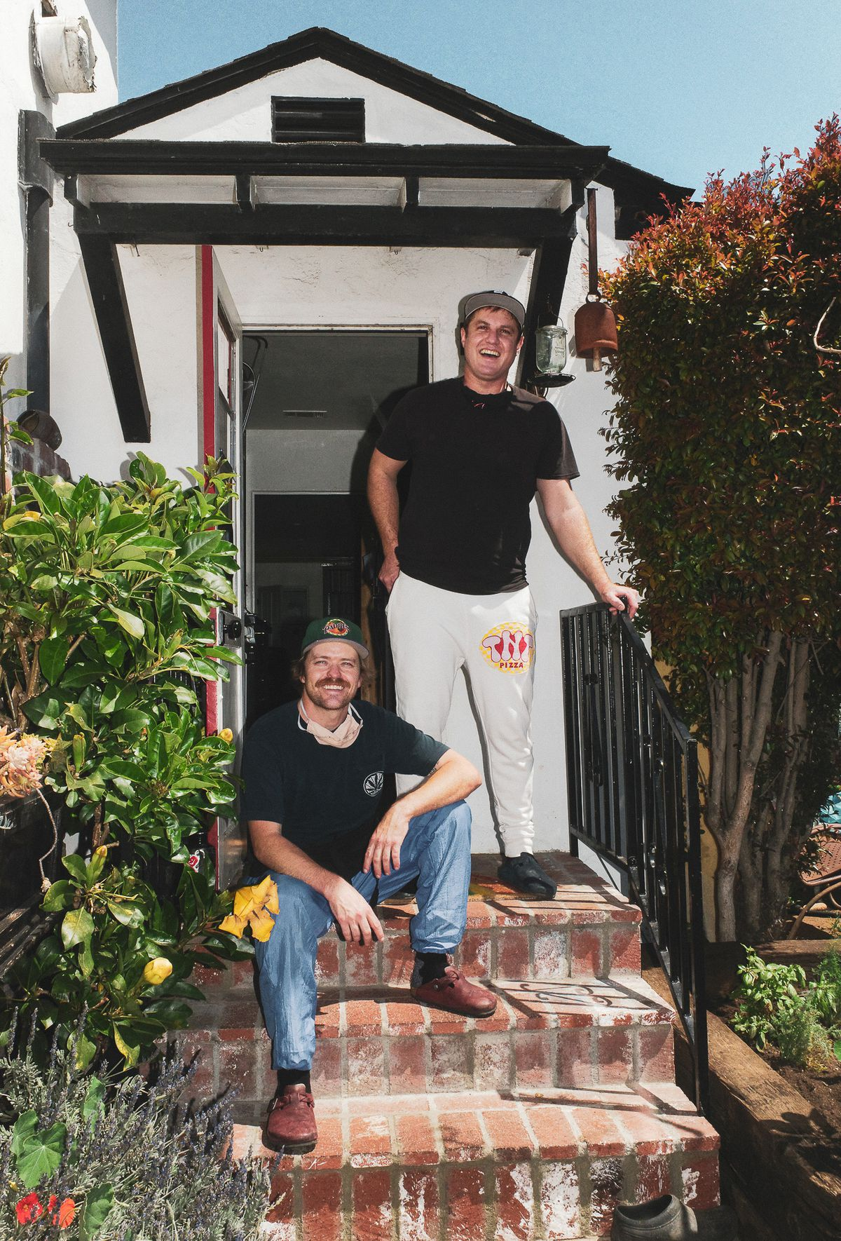 Tnt Pizza owners Kevin Gist and Joseph Ghafouri Wehrly in front of a house